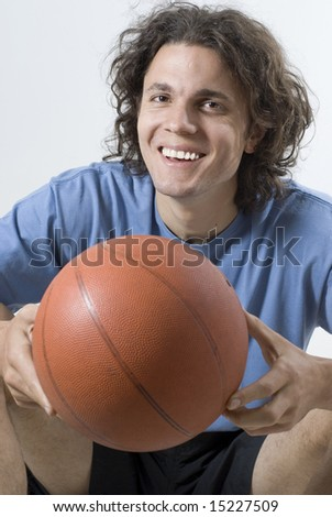 Smiling man sitting and holding a basketball. Vertically framed photograph - stock photo