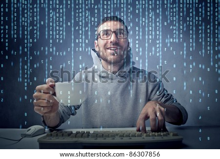 Smiling man sitting in front of a computer screen and holding a cup of coffee - stock photo
