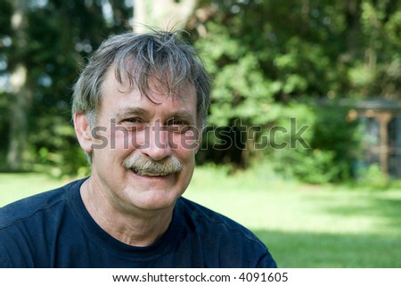 smiling man, sitting in his backyard - stock photo