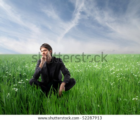 Smiling man sitting on a green meadow - stock photo