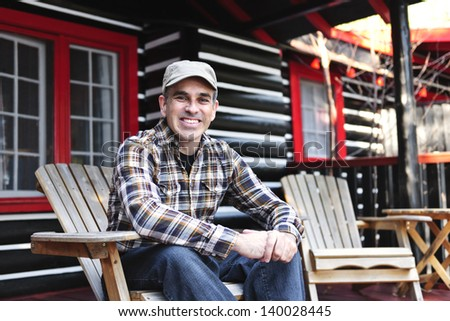 Smiling man sitting on cottage deck in wooden adirondack chair - stock photo