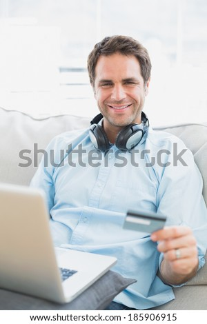 Smiling man sitting on sofa online shopping with laptop at home in the living room