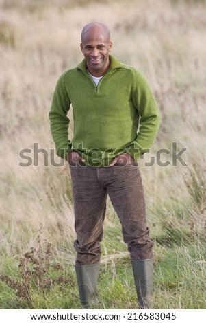 Smiling man standing in field with hands in pockets