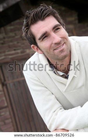 Smiling man standing in front of countryhouse