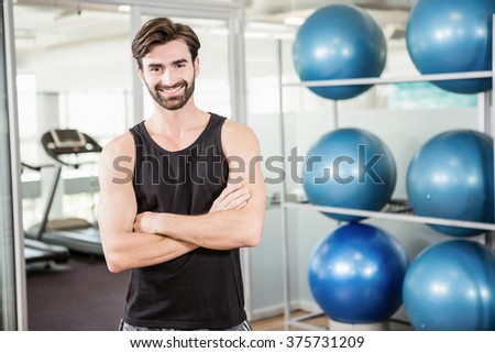 Smiling man standing with arms crossed in the gym - stock photo