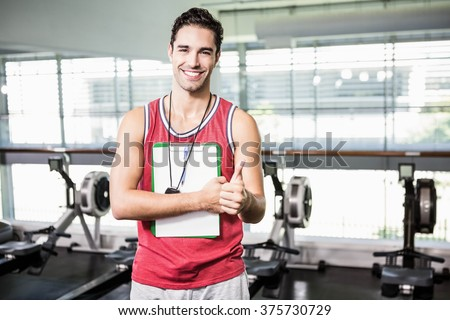 Smiling man standing with clipboard and stopwatch and showing thumb up in the gym - stock photo