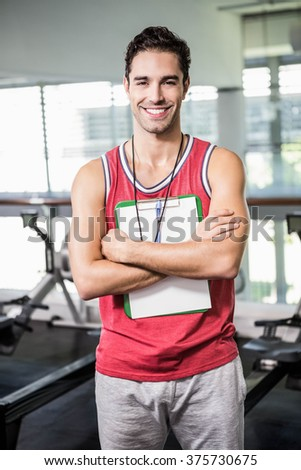 Smiling man standing with clipboard and stopwatch in the gym - stock photo