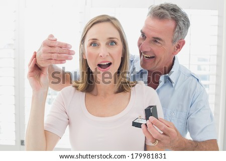 Smiling man surprising happy woman with a wedding ring at home - stock photo