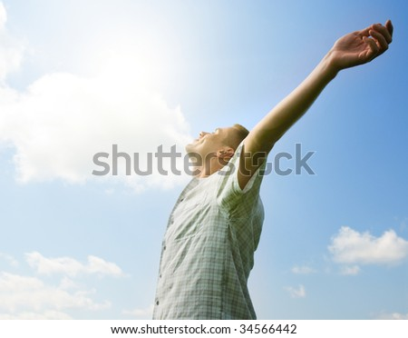 smiling man taking energy from sun