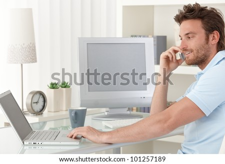 Smiling man talking on mobile phone while using laptop computer at desk in study. Blank space on screens for your logo or image. - stock photo