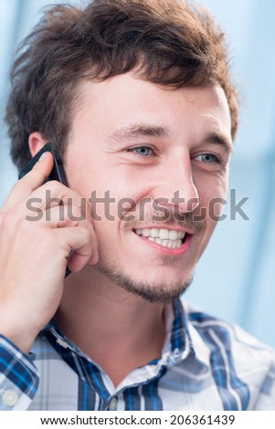 Smiling man talking on the phone - stock photo