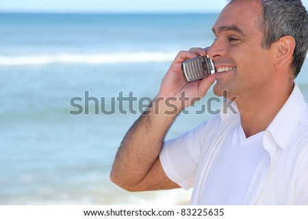 Smiling man using a cellphone by the ocean - stock photo