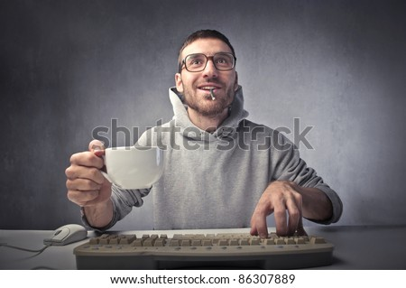 Smiling man using a computer and holding a cup of coffee
