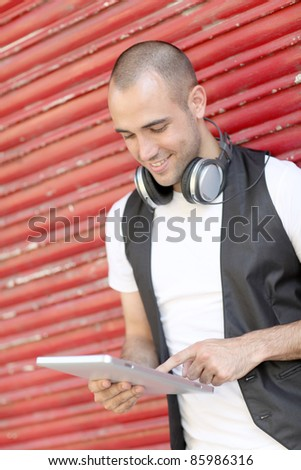 Smiling man using electronic tablet in the street - stock photo