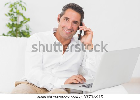 Smiling man using his laptop and phoning in the living room - stock photo
