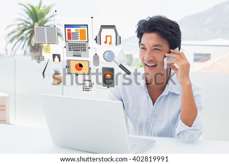 Smiling man using his laptop and talking on phone against media devices with cloud