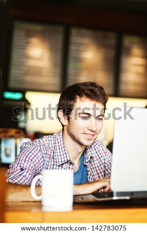 smiling man using laptop in the cafe - stock photo