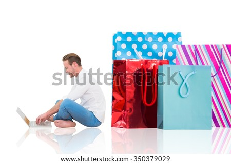 Smiling man using laptop with crossed legs against white background with vignette