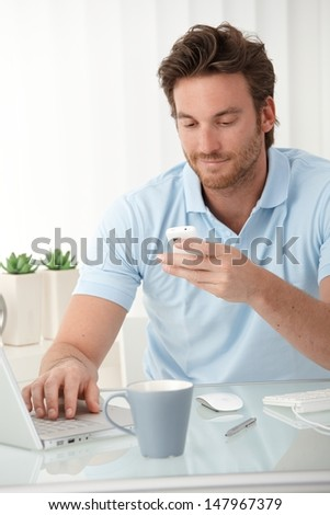 Smiling man using mobile phone for texting, typing on laptop computer, sitting at desk. - stock photo