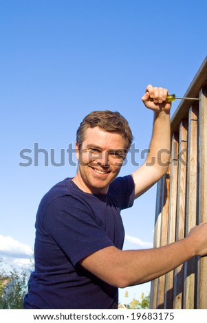Smiling man using screwdriver to fix porch. Vertically framed photo. - stock photo