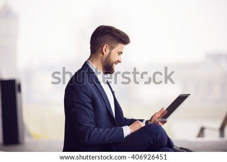 Smiling man using tablet - stock photo