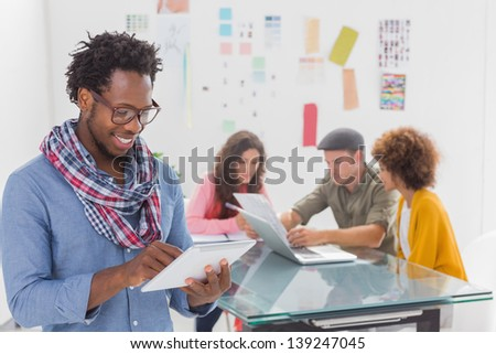 Smiling man using tablet with creative team working behind in modern office - stock photo