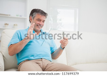 Smiling man using video chat waving at clear pane as digital tablet pc - stock photo