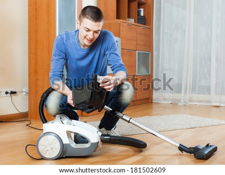 Smiling man  vacuuming with vacuum cleaner on parquet floor in living room - stock photo