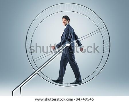 smiling man walking in hamster wheel - stock photo