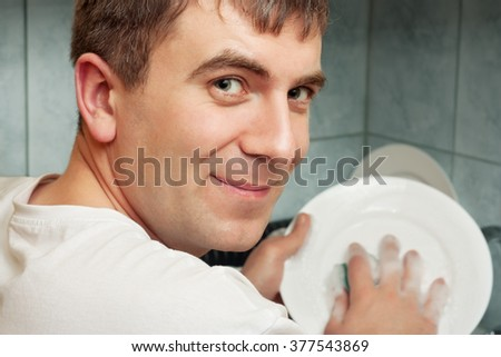 Smiling man washing dish in the kitchen - stock photo