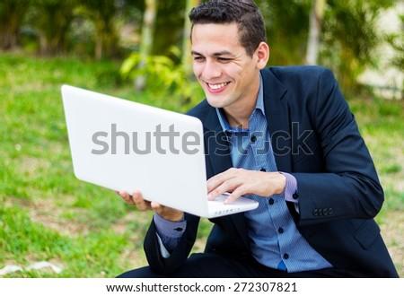 smiling man watching his laptop outdoor - stock photo