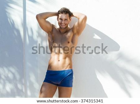 Smiling man wear blue swimming trunks - stock photo