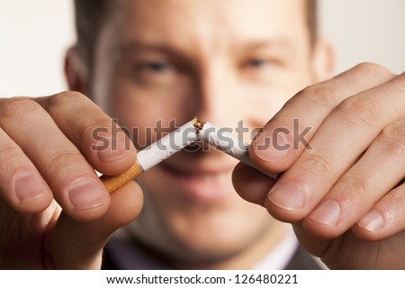 smiling man with a blurred face breaks a cigarette