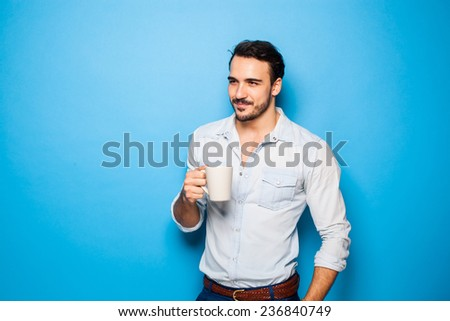 smiling man with a cup of coffee in hand, standing on blue background - stock photo