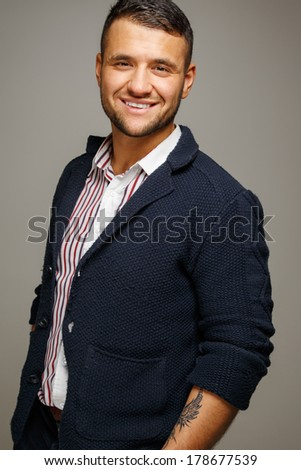 Smiling man with a tattoo wearing a striped shirt - stock photo