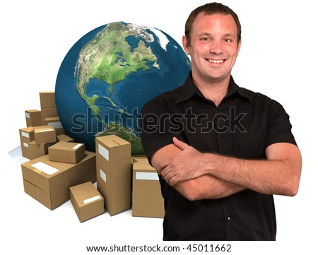 Smiling man with a world map and lots of cardboard boxes in the background - stock photo