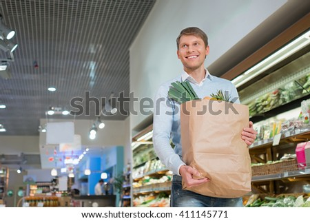 Smiling man with bag indoors - stock photo