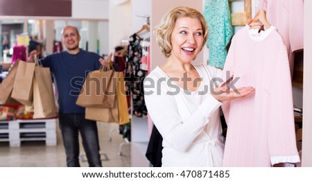 Smiling man with bags waiting for mature woman selecting dress in boutique