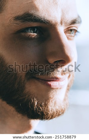 smiling man with beard in sunlight at home