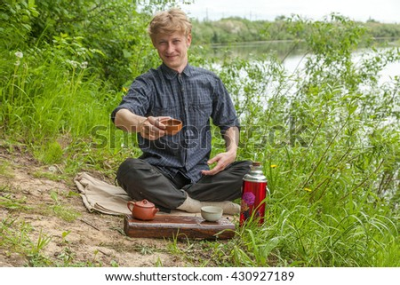 Smiling man with blonde hair giving you a cup of chinese tea