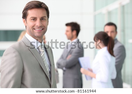 Smiling man with colleagues outside office building - stock photo