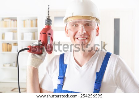 Smiling man with electric drill wearing protective helmet and glasses - stock photo