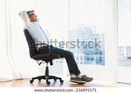 Smiling man with glasses sitting on office chair and relaxing at apartment - stock photo