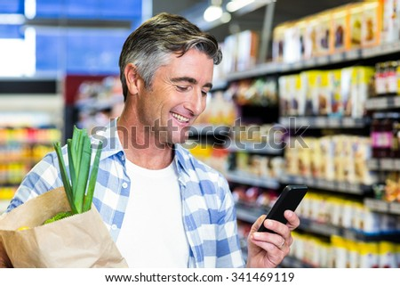 Smiling man with grocery bag using smartphone at the supermarket - stock photo