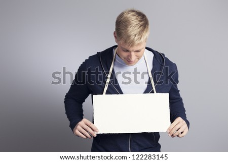 Smiling man with head down looking at white empty signboard with space for text while holding it, isolated on grey background. - stock photo