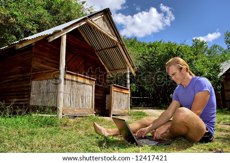 Smiling man with laptop on grass next to rural house. Shot in Sodwana, KwaZulu-Natal province, South Africa.