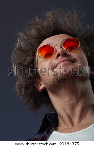 Smiling man with round hippie sunglasses and long hair - stock photo