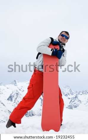 Smiling man with snowboard in red pants - stock photo