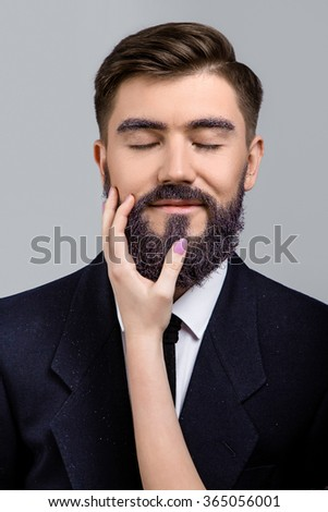 Smiling man, with violet beard, wearing in dark blue suit and tie, posing with closed eyes with woman's hand near his face, on white background, in studio, close up - stock photo