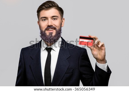 Smiling man, with violet beard, wearing in dark blue suit and tie, posing with credit card, on gray background, in studio, waist up - stock photo